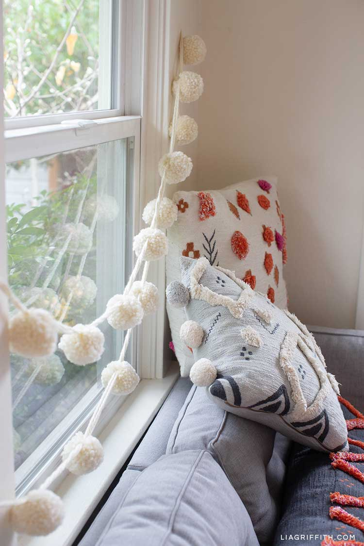 jumbo pom-pom garland in white hanging across window and behind couch and pillows