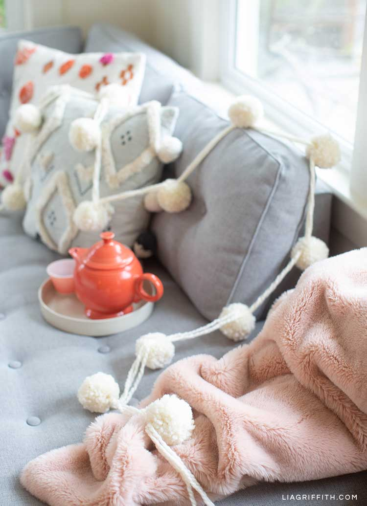 white jumbo pom-pom garland draped across grey couch, pillows, and pink fleece blanket
