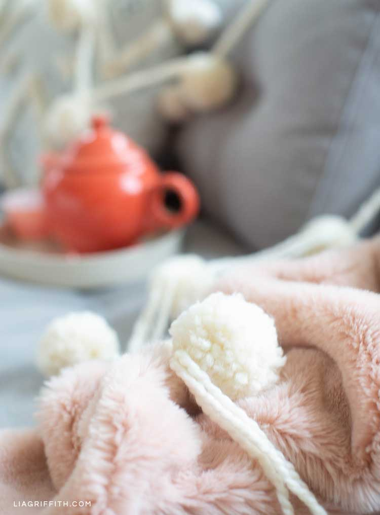 jumbo pom-pom garland across couch and pink blanket with teapot in background