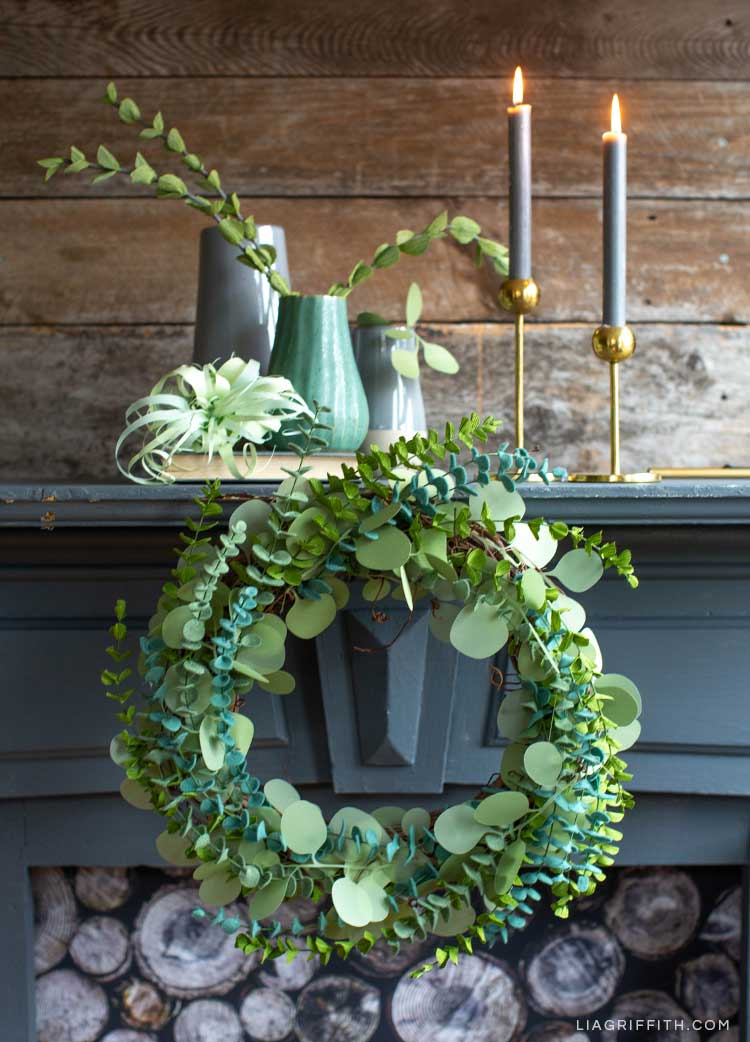 Paper and felt eucalyptus wreath on mantel by vases, paper air plant, and candlesticks