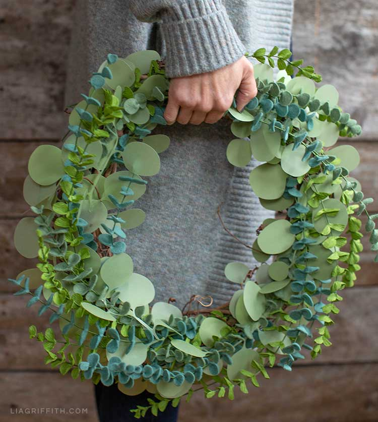 Woman holding paper and felt eucalyptus wreath