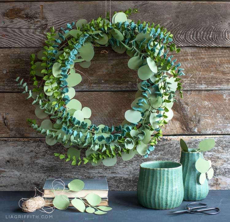 Paper and felt eucalyptus wreath on wood wall next to vases and books