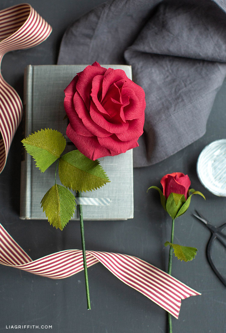 Crepe paper ruby rose flower and rosebud next to book and ribbon