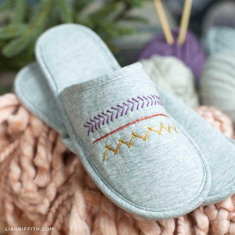 DIY embroidered slippers on pink blanket with yarn in background