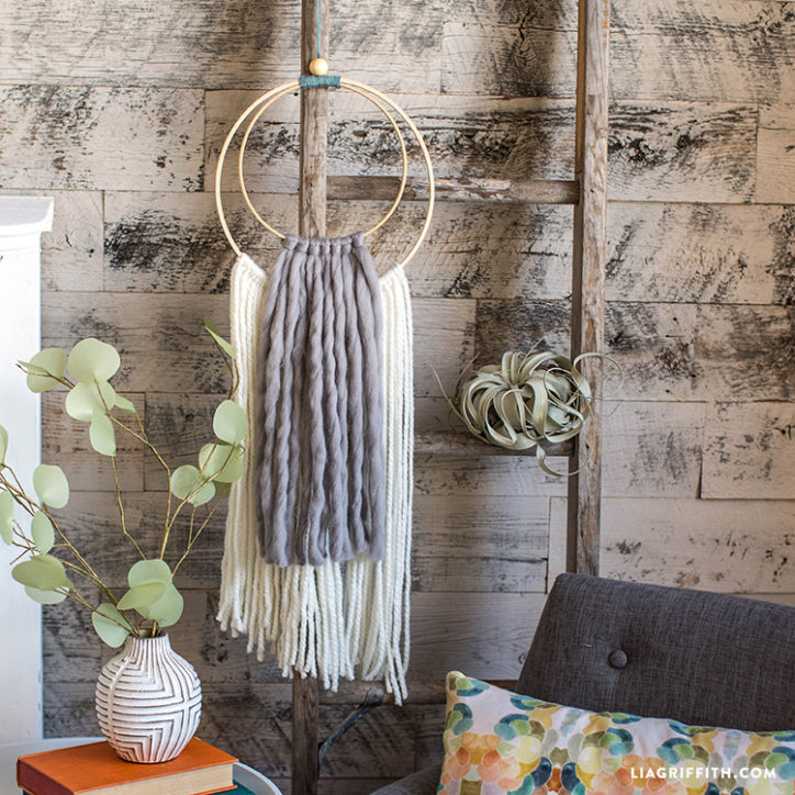 DIY wool yarn wall hanging in living room next to paper plants