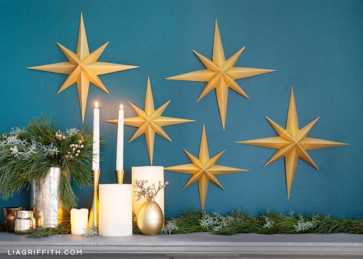 3D paper stars on blue wall above mantel with greenery, candles, and small gold vase