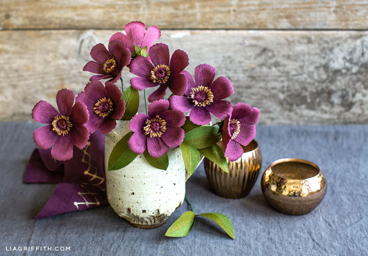crepe paper chocolate cosmos in white pot with tiny, empty gold vases nearby