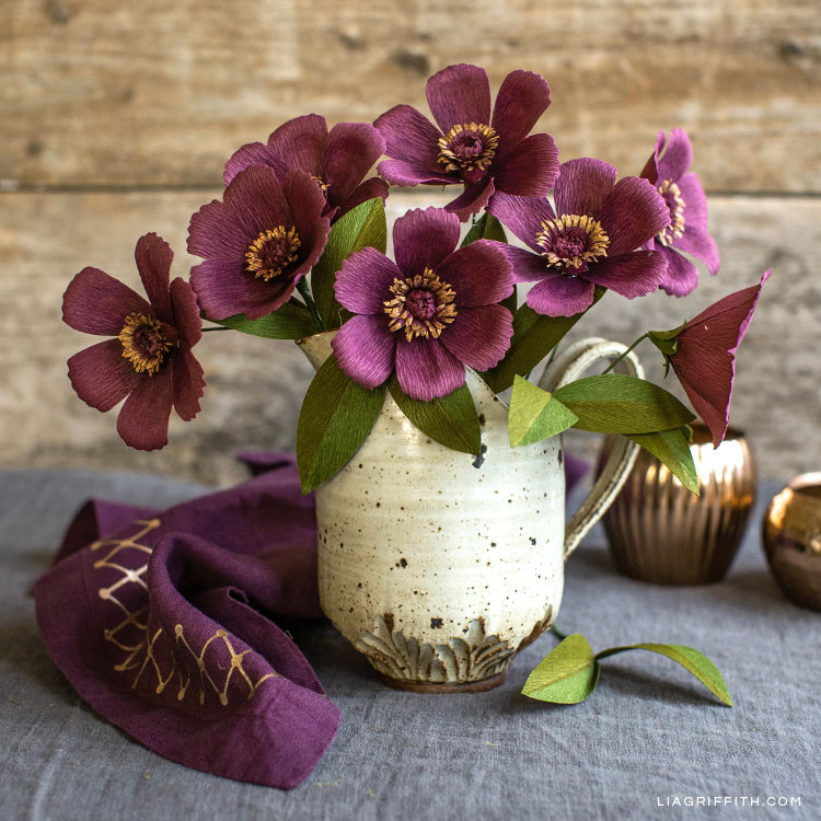 crepe paper chocolate cosmos in white pot next to DIY linen and empty gold vases