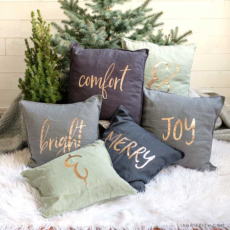 comfort & joy and merry & bright DIY holiday pillows on faux fur blanket in front of Christmas trees