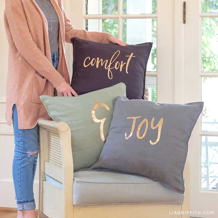 Woman holding comfort & joy holiday pillows propped on chair