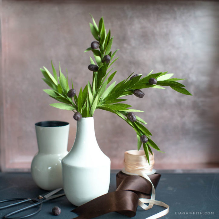 crepe paper olive branches in white vase next to empty vases
