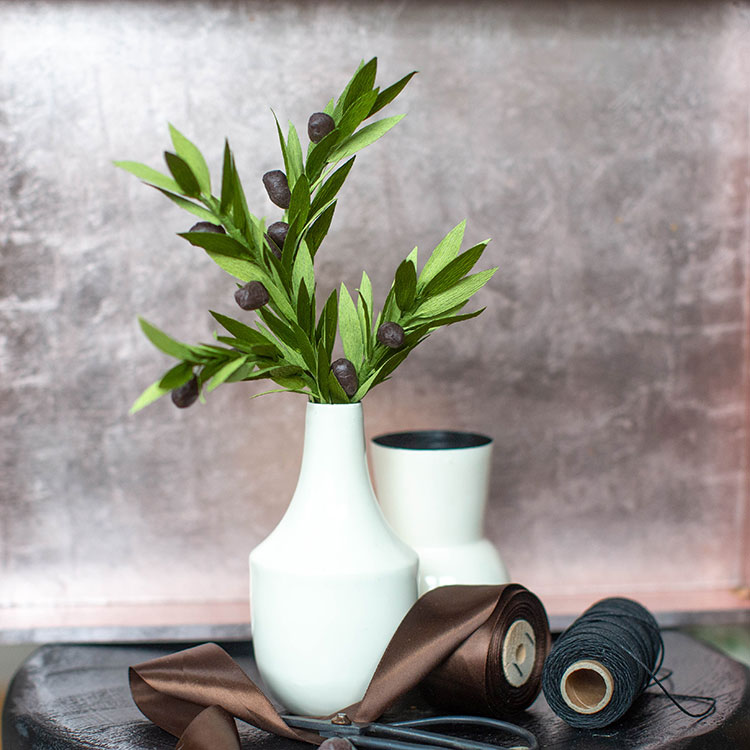 crepe paper olive branches in white vase with brown ribbon and black thread