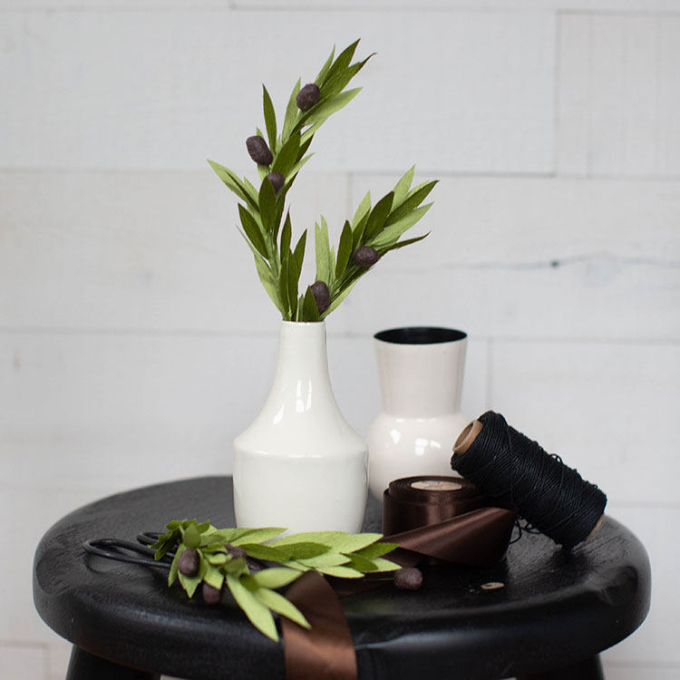 crepe paper olive branches in white vase on stool with brown ribbon, black thread, empty vase, scissors, and more olive branches