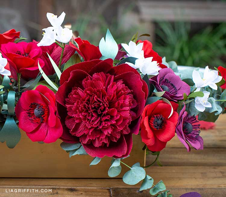 crepe paper red charm peony, paper anemones, paperwhites, and eucalyptus in floral centerpieces