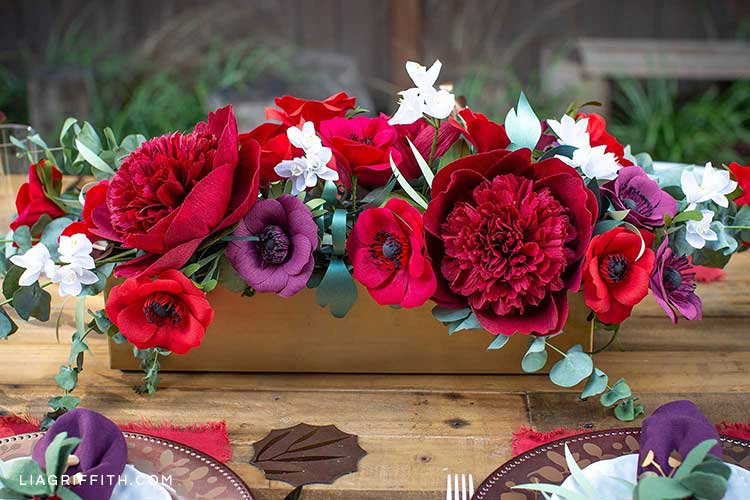 Paper red charm peonies, plum anemones, and paperwhites in floral arrangement centerpiece on table