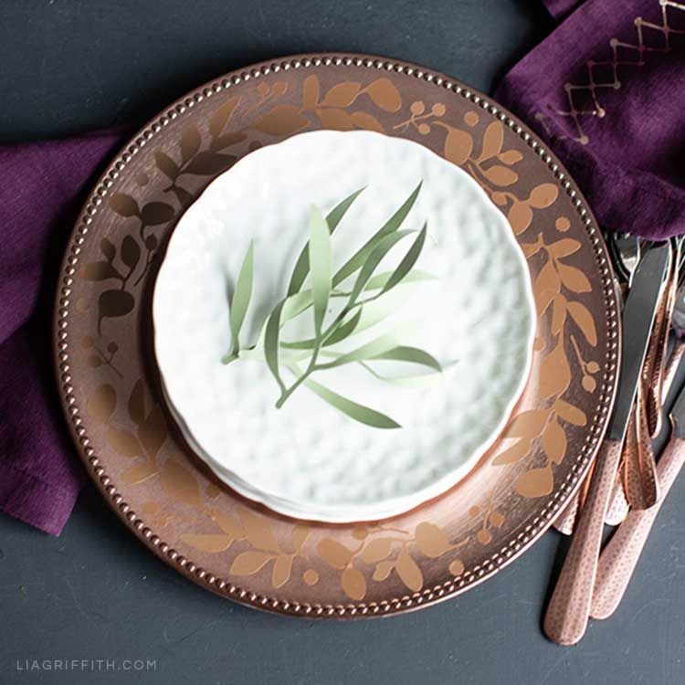 Charger plate with vinyl decal, white plate, paper leaf décor, purple linens, and utensils