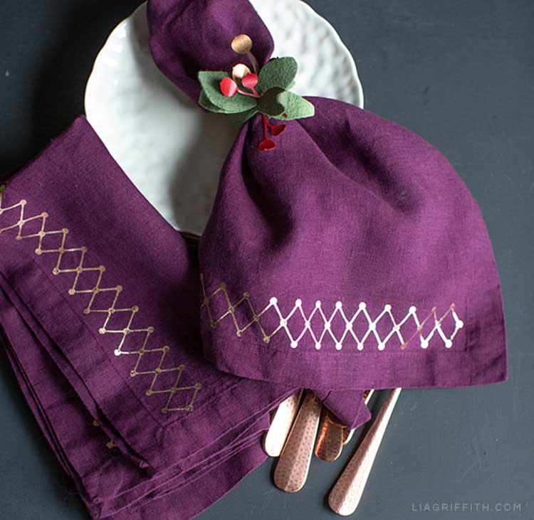 Plum linens with DIY iron-on design and felt leaf napkin ring with paper berries