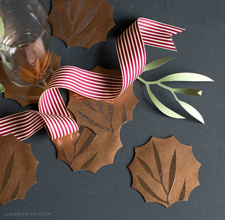 Leather coasters with DIY leaf designs next to ribbon, glass, and paper leaf