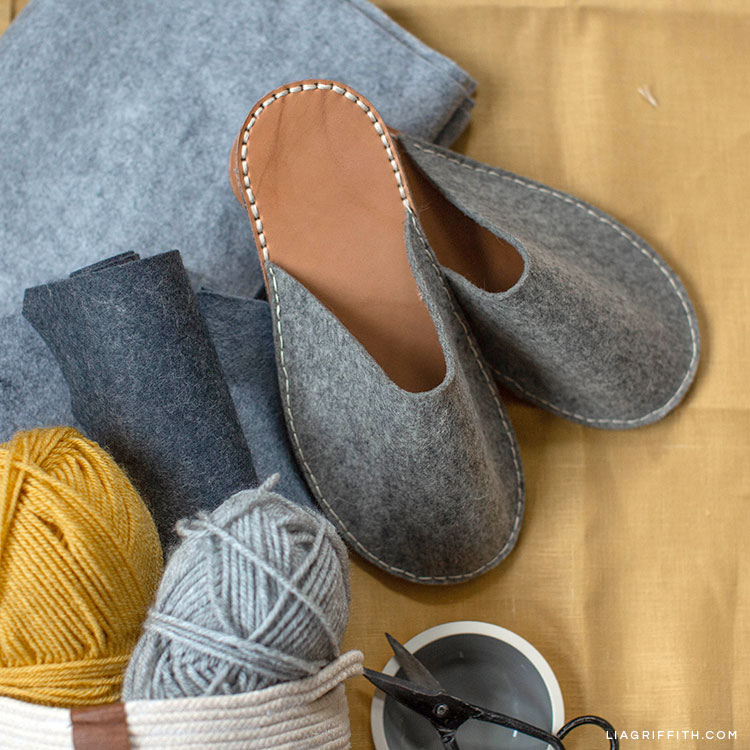 DIY felt and leather slippers next to yarn, felt, and scissors