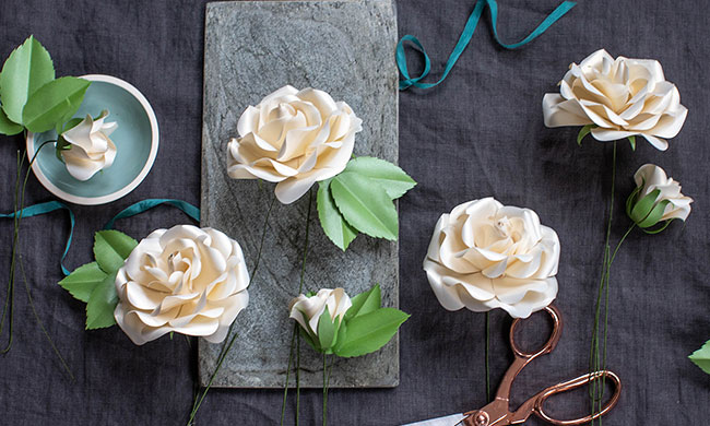 off-white frosted paper Ecuadorian roses with stems on table with ribbon and scissors