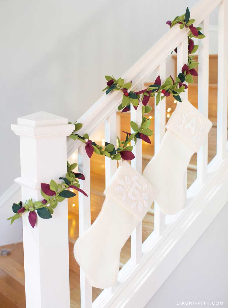 felt greenery garland on staircase banister with white stocking