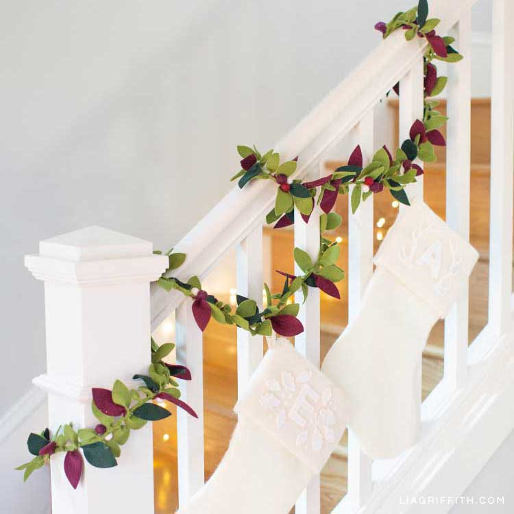 felt greenery garland on white staircase with white stockings