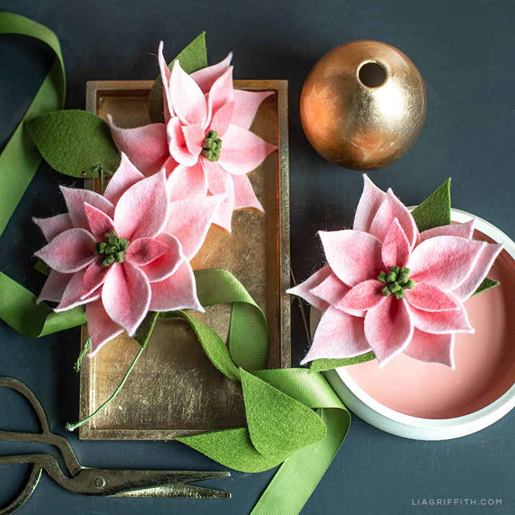 pink felt poinsettia plants on gold tray and in white bowl with green ribbon, empty gold vase, and scissors