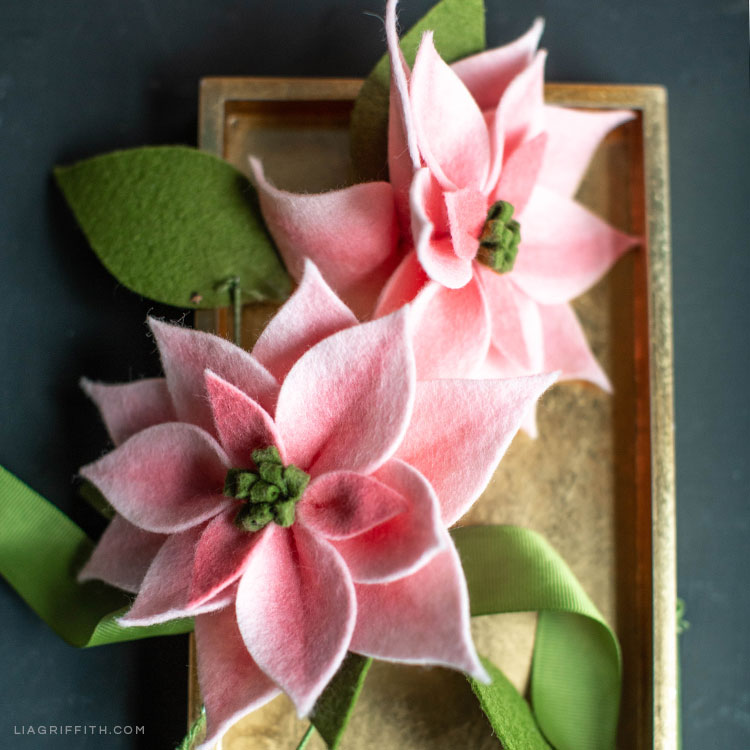 pink felt poinsettia plants on gold tray