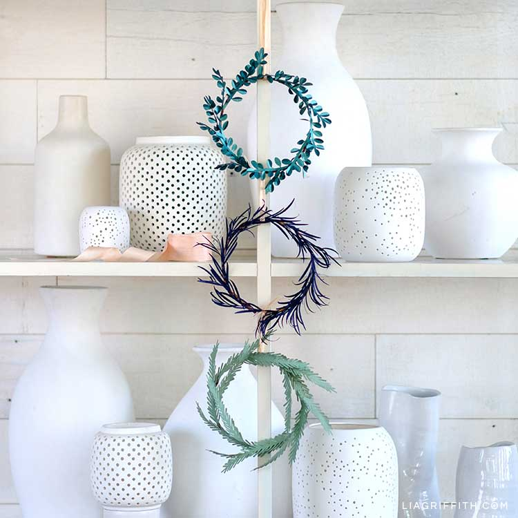 mini evergreen paper wreaths hanging on open shelves