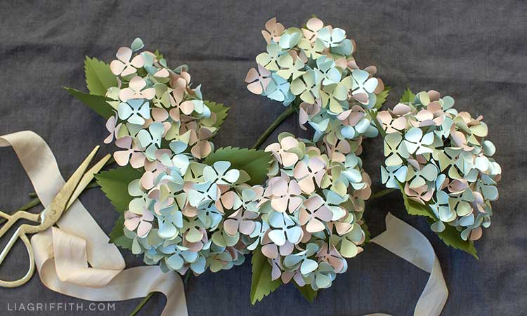 frosted paper hydrangeas on top of grey sheet next to gold scissors and cream ribbon