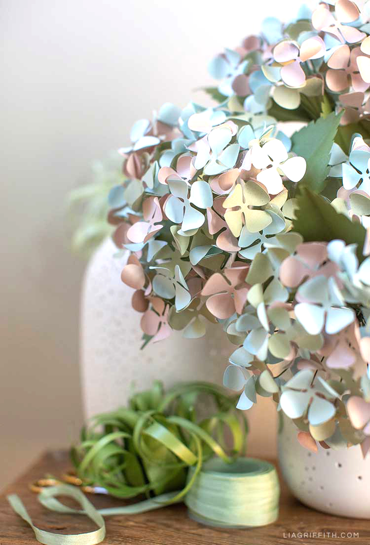 frosted paper hydrangeas in white planter next to paper air plant and green ribbon