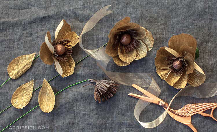 gold crepe paper anemones with translucent ribbon and copper scissors