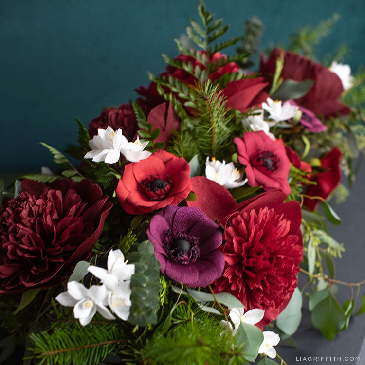 crepe paper red charm peonies, red and purple anemones, and paperwhite flowers with fresh pine, eucalyptus, and ferns