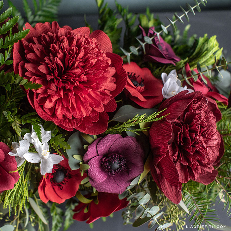 crepe paper red charm peonies, anemones, and paperwhites with fresh greenery