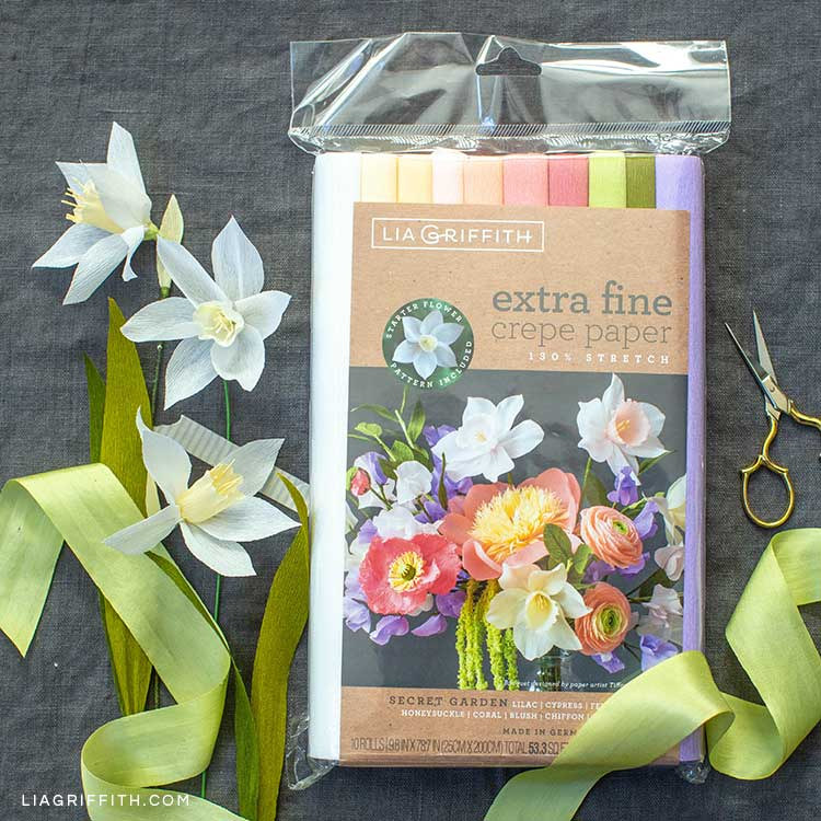 Lia Griffith extra-fine crepe paper Secret Garden collection next to crepe paper jonquil flowers, green ribbon, and scissors