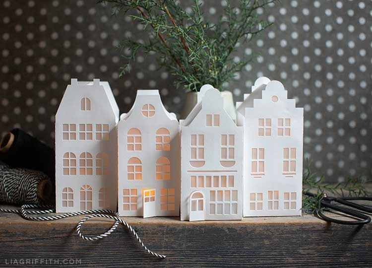 paper canal houses on mantel with fresh greenery, scissors, and twine