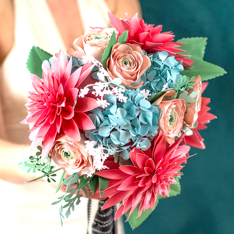 woman holding frosted paper bridal bouquet with coral dahlias, peach ranunculus, blue hydrangeas, seeded eucalyptus, and dusty miller leaves