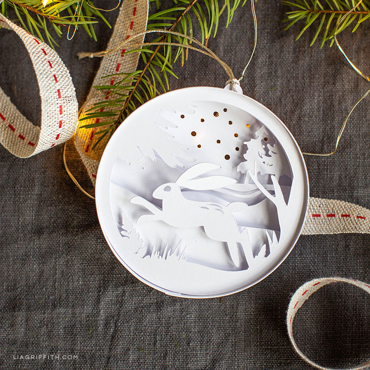 3D paper woodland ornament featuring a rabbit hopping in the snow