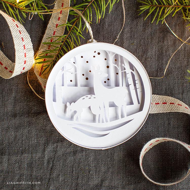 3D paper woodland ornament featuring two deers in the snow in front of trees
