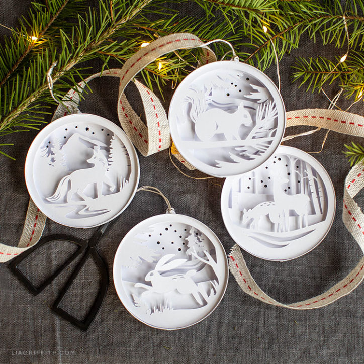paper woodland ornaments next to pine branches, ribbon, and scissors