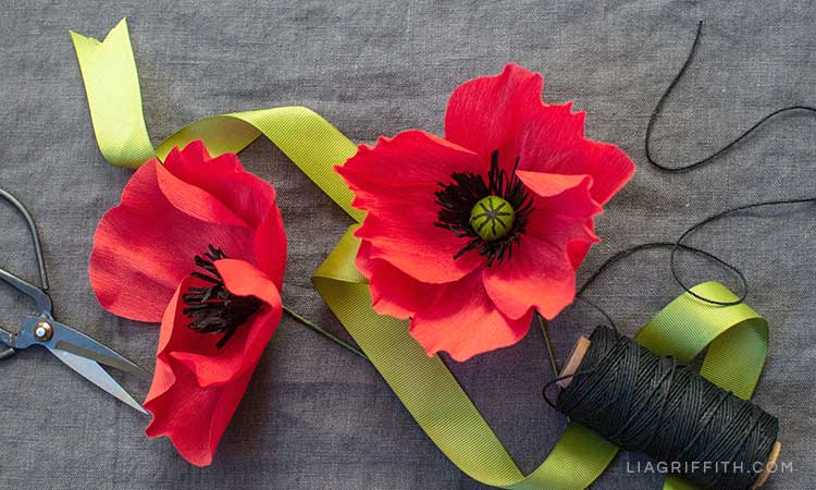 extra fine crepe paper poppy flowers with green ribbon, scissors, and black thread