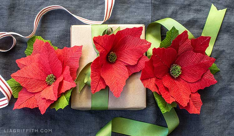 heavy crepe paper poinsettia flowers as gift toppers