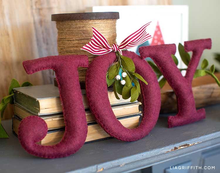 JOY felt word with crepe paper mistletoe on mantel next to books