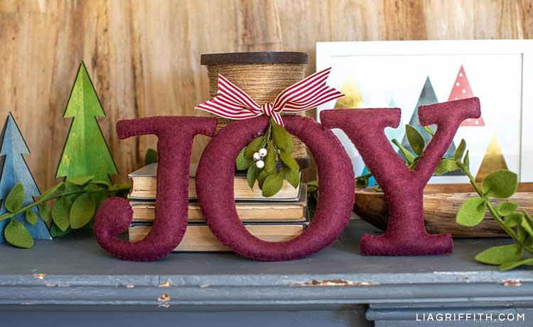 JOY felt word with crepe paper mistletoe on mantel next to books, mini trees, and framed holiday art