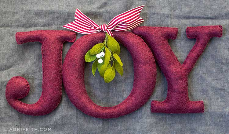 Holiday décor felt letters spelling out JOY with ribbon and crepe paper mistletoe