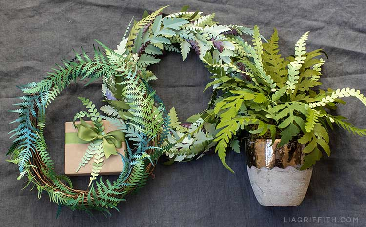 Paper fern arrangements including paper fern wreaths, potted paper fern plant, and paper fern leaves on gift