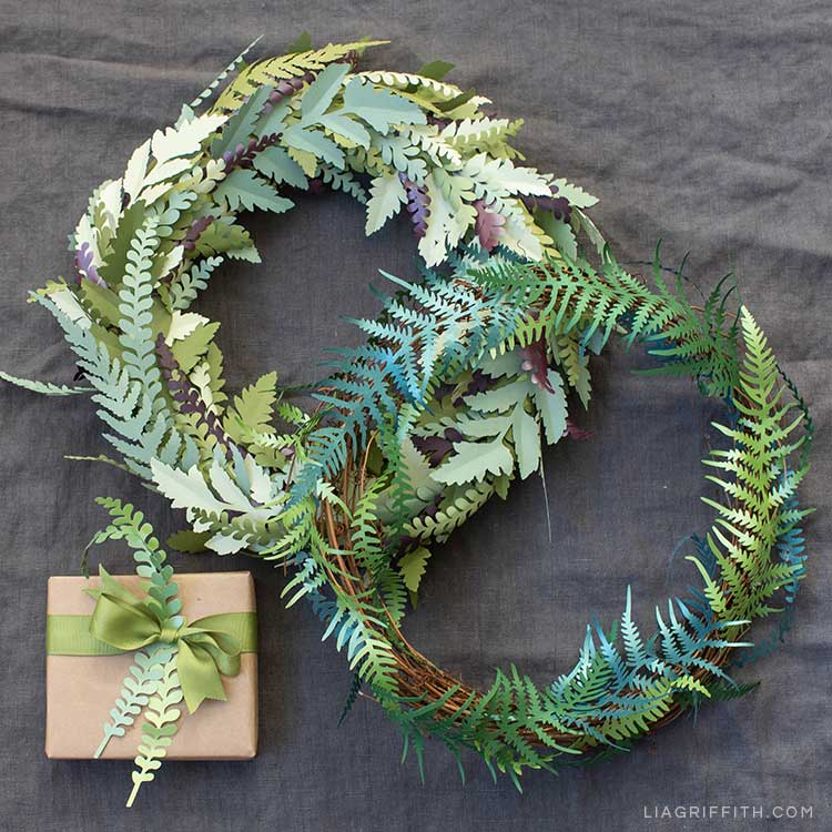 Paper fern wreaths and paper fern leaves tucked in bow on gift