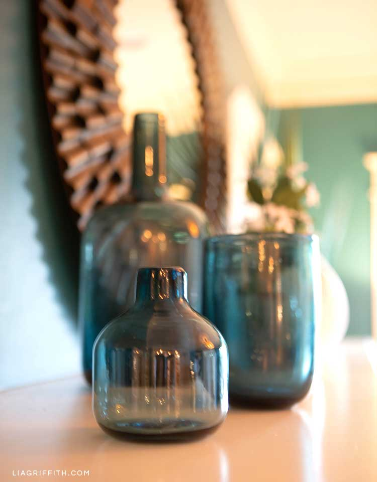Clear blue vases on fireplace mantel with mirror in background
