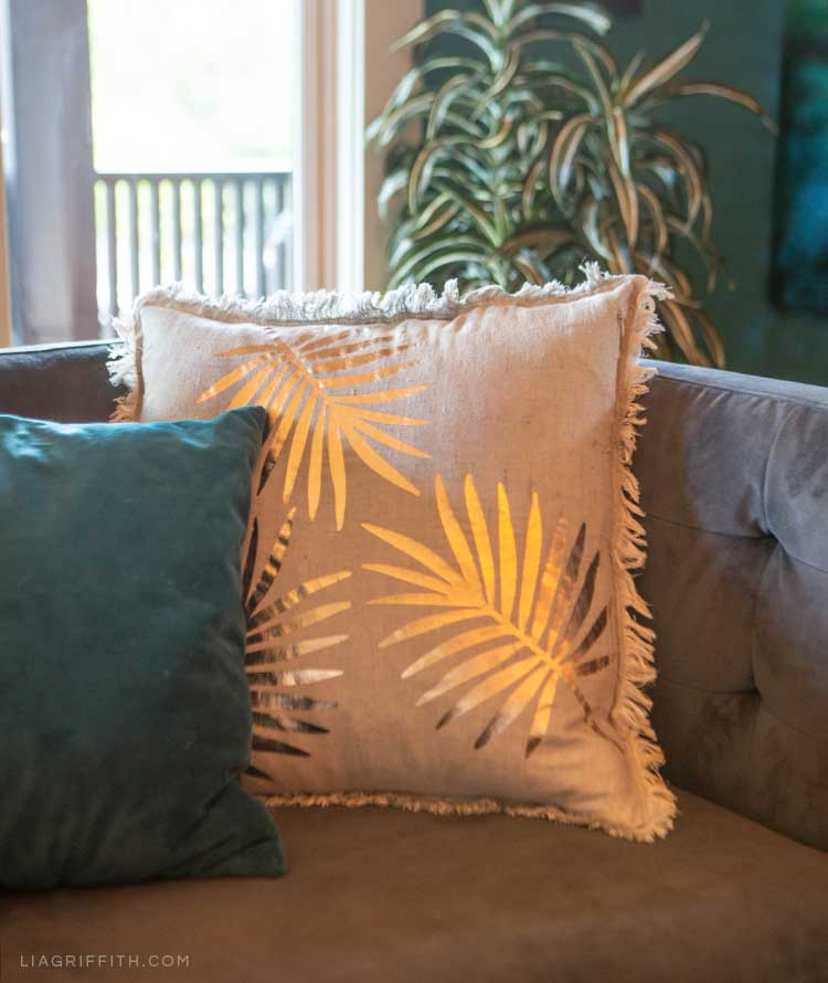 DIY tropical pillow and DIY teal velvet pillow on couch