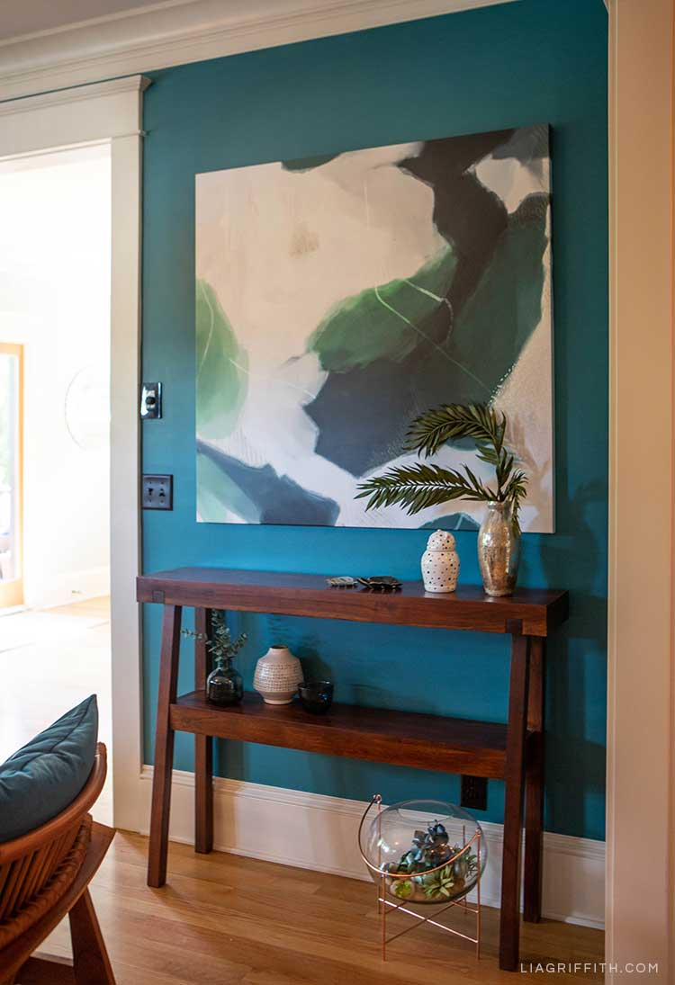 console table next to dark blue wall and canvas art